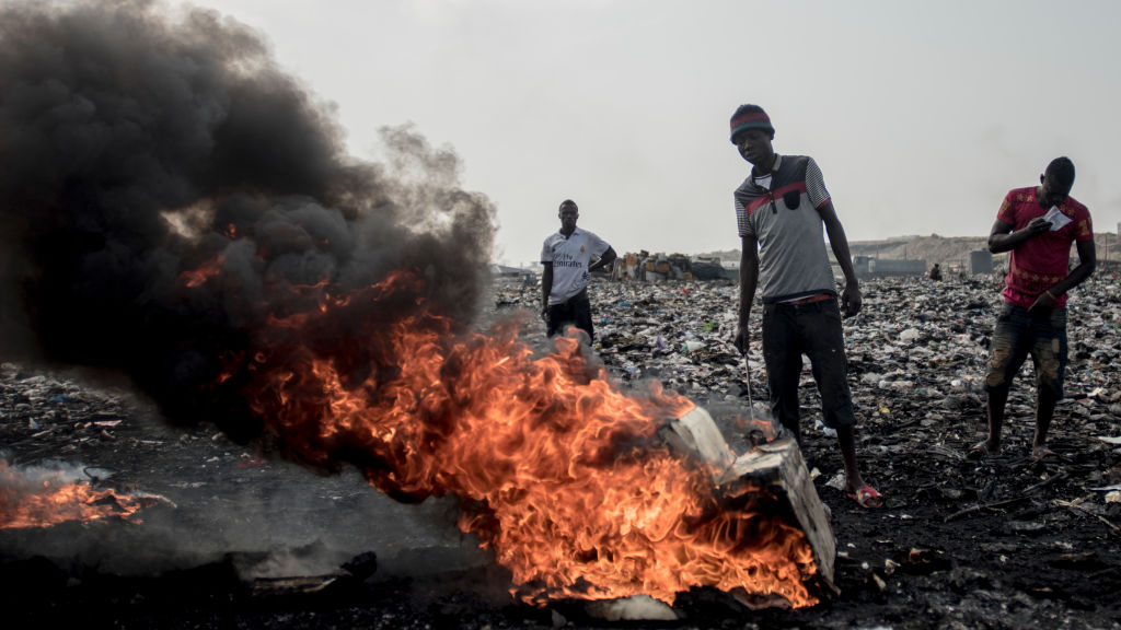 Workers burns electronic waste at Agbogboshie, an e-waste dump site in Ghana. (Photo by Cristina Aldehuela/AFP/Getty Images)