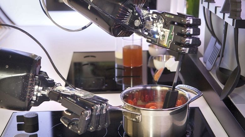 Robotic hands preparing a meal on a stovetop.