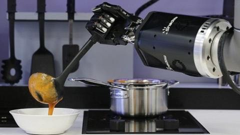 Robotic arms serve a soup prepared on stovetop.