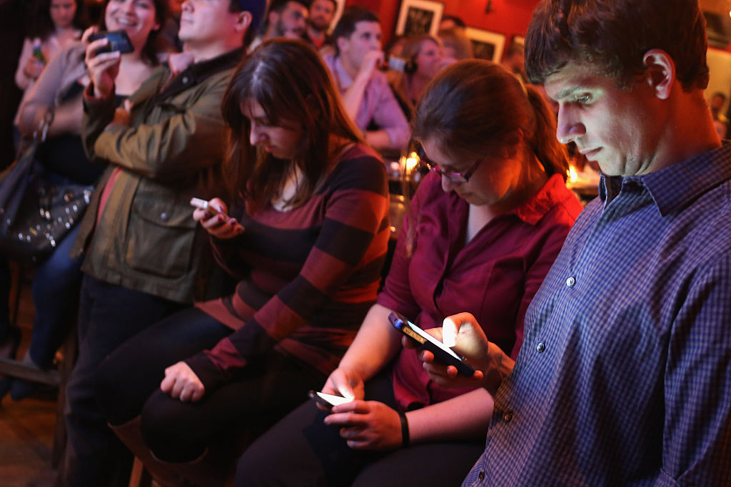 Party attendees on smartphones (Credit: Getty Images)