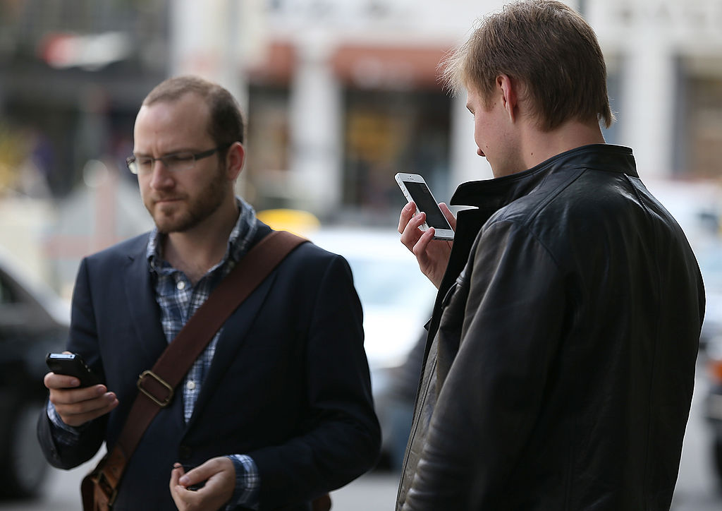 Guys on smartphones (Credit: Getty Images)