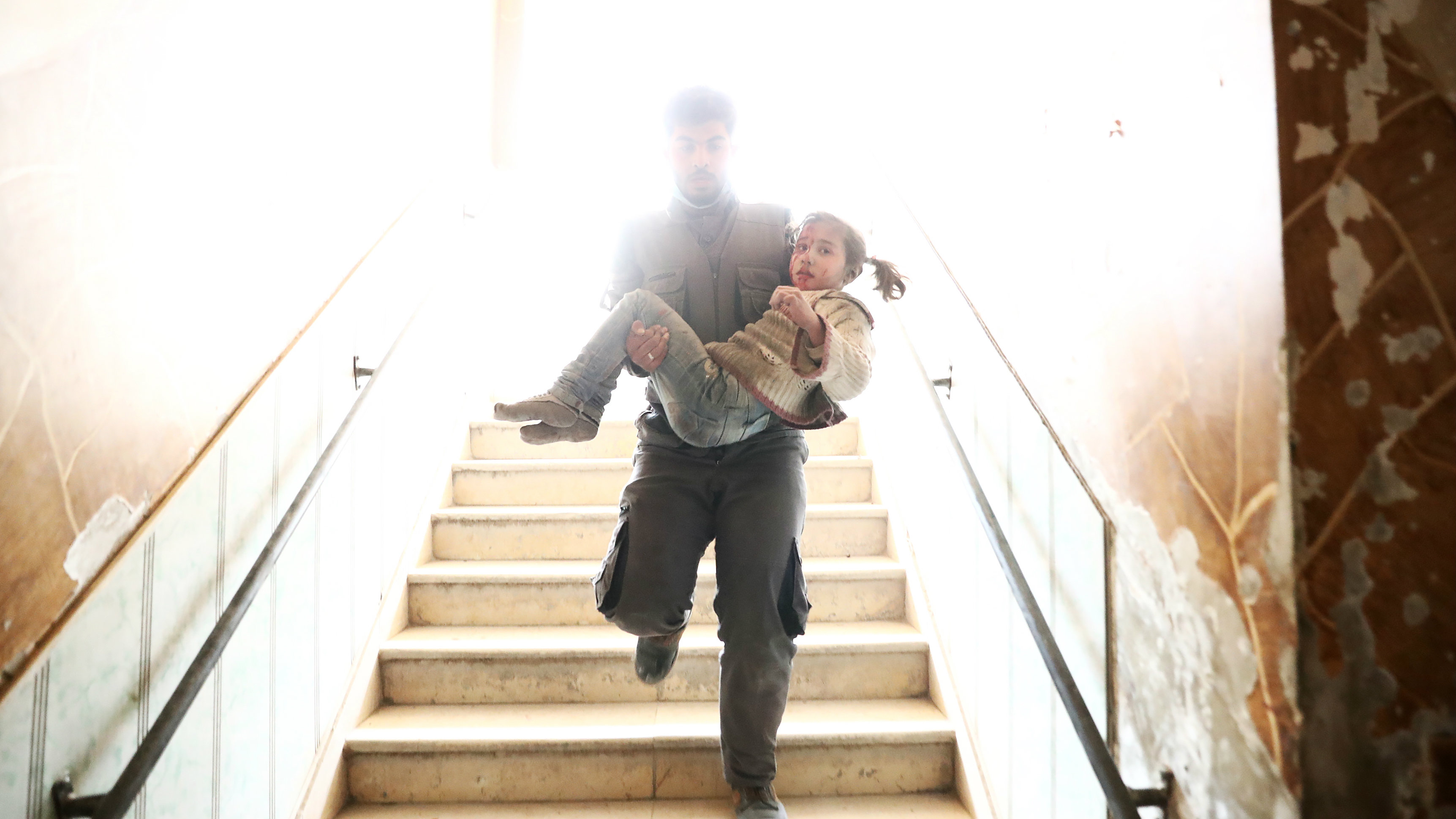 TOPSHOT - A Syrian civil defence volunteer carries a wounded girl as he rushes to a make-shift hospital following reported government airstrike on the rebel-held town of Douma, on the eastern outskirts of the capital Damascus, on February 25, 2017. Syrian regime forces carried out raids on several areas in the country, targeting mainly the besieged town of Douma, causing the deaths of at least 13 civilians, according to Syrian Observatory for Human Rights. The raids continued despite the United Nations confirmation a few days earlier that Moscow formally asked its ally Damascus to stop launching strikes during the Geneva negotiations, which began earlier in the week. / AFP / Abd Doumany (Photo credit should read ABD DOUMANY/AFP/Getty Images)