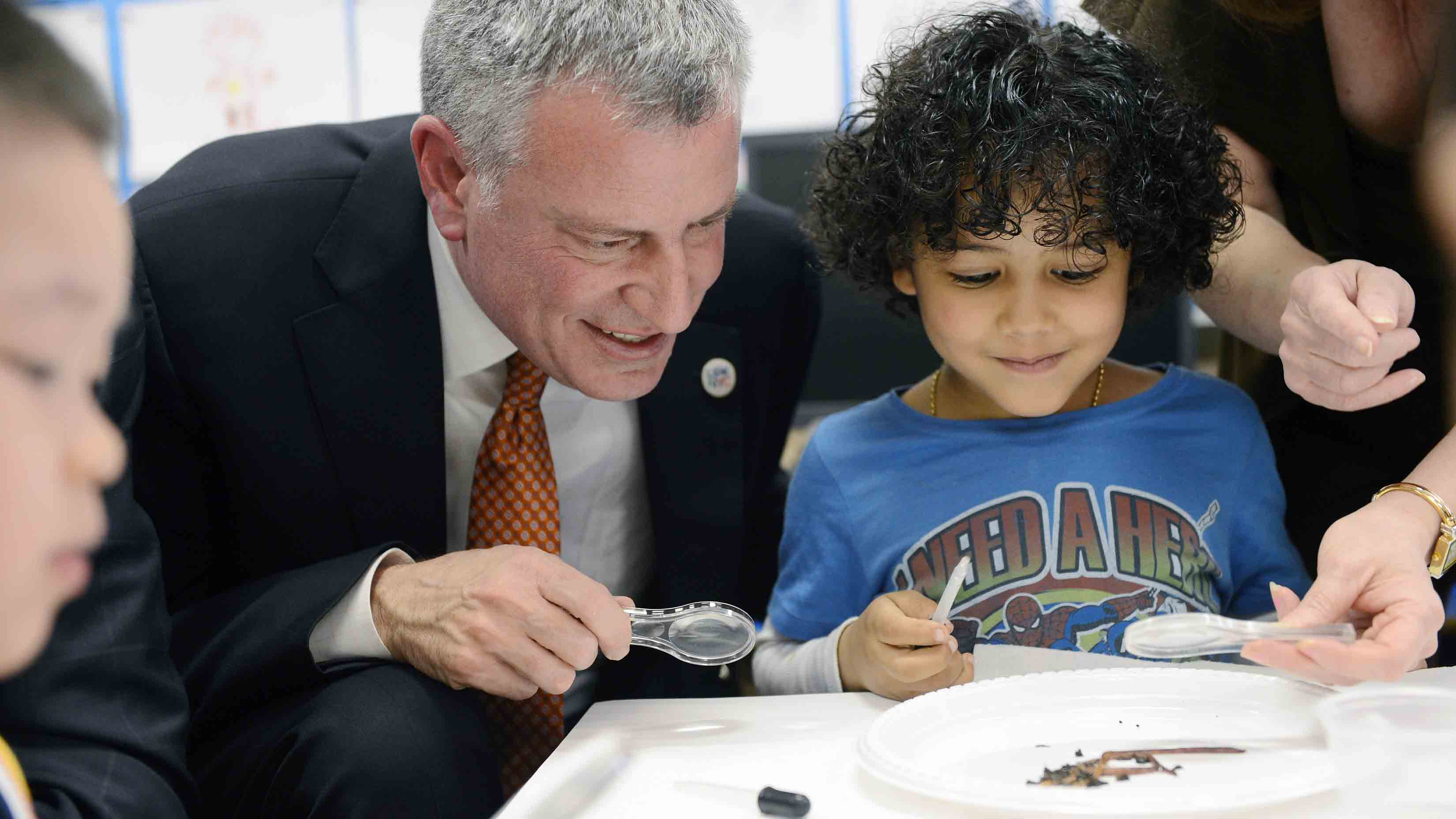 New York City Mayor Bill de Blasio and student Justin De La Cruz work on a science project with worms