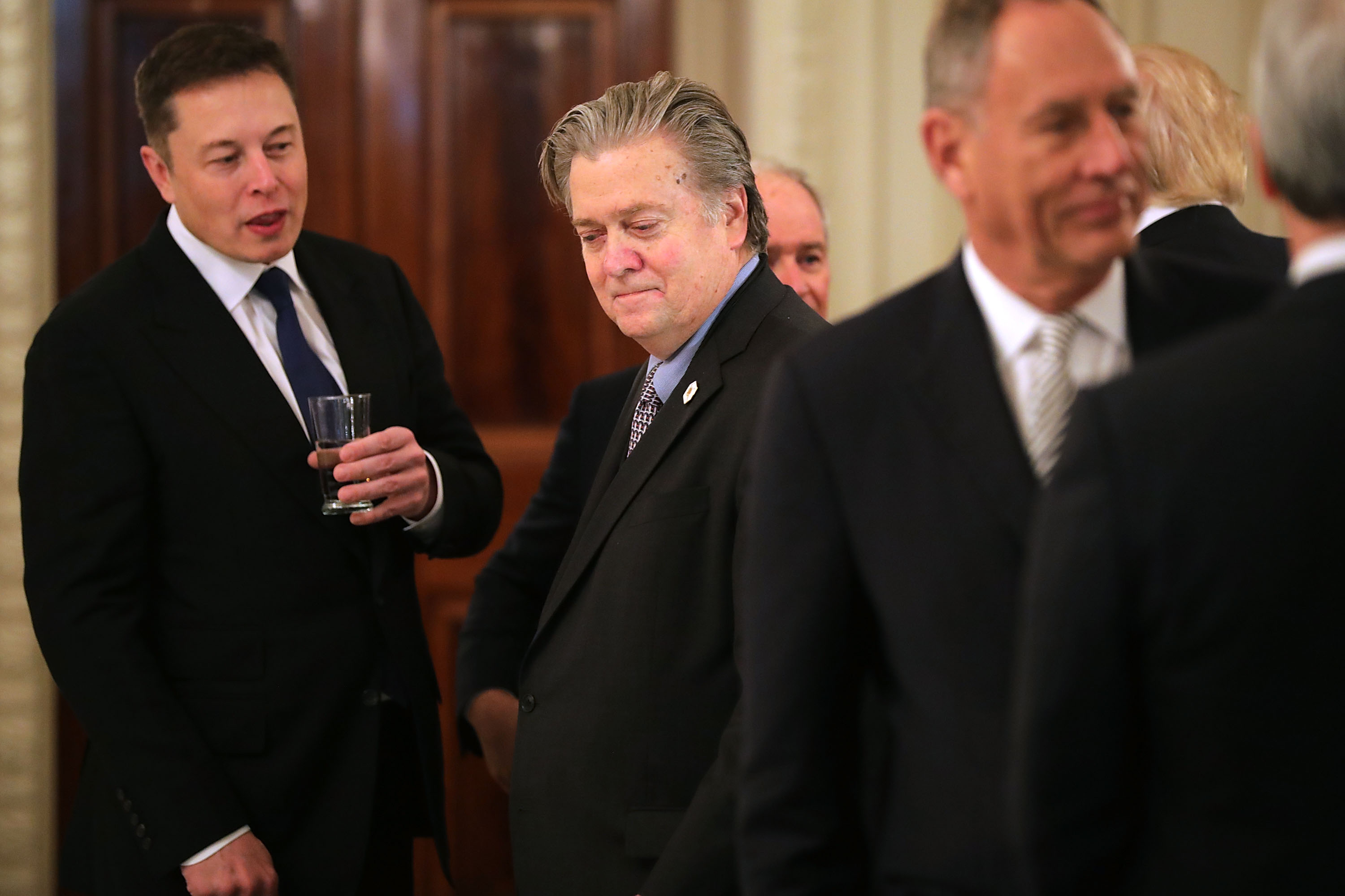 WASHINGTON DC- FEBRUARY 03 SpaceX and Tesla CEO Elon Musk talks with White House Chief Strategist Steve Bannon at the beginning of a policy forum with U.S. President Donald Trump in the State Dining Room at the White House